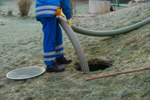 Man working on septic tank on property with frosted grass